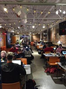 A room full of people working on games at laptops